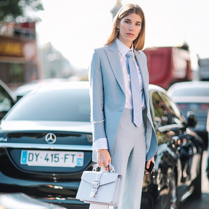 a woman in a business suit standing in front of cars