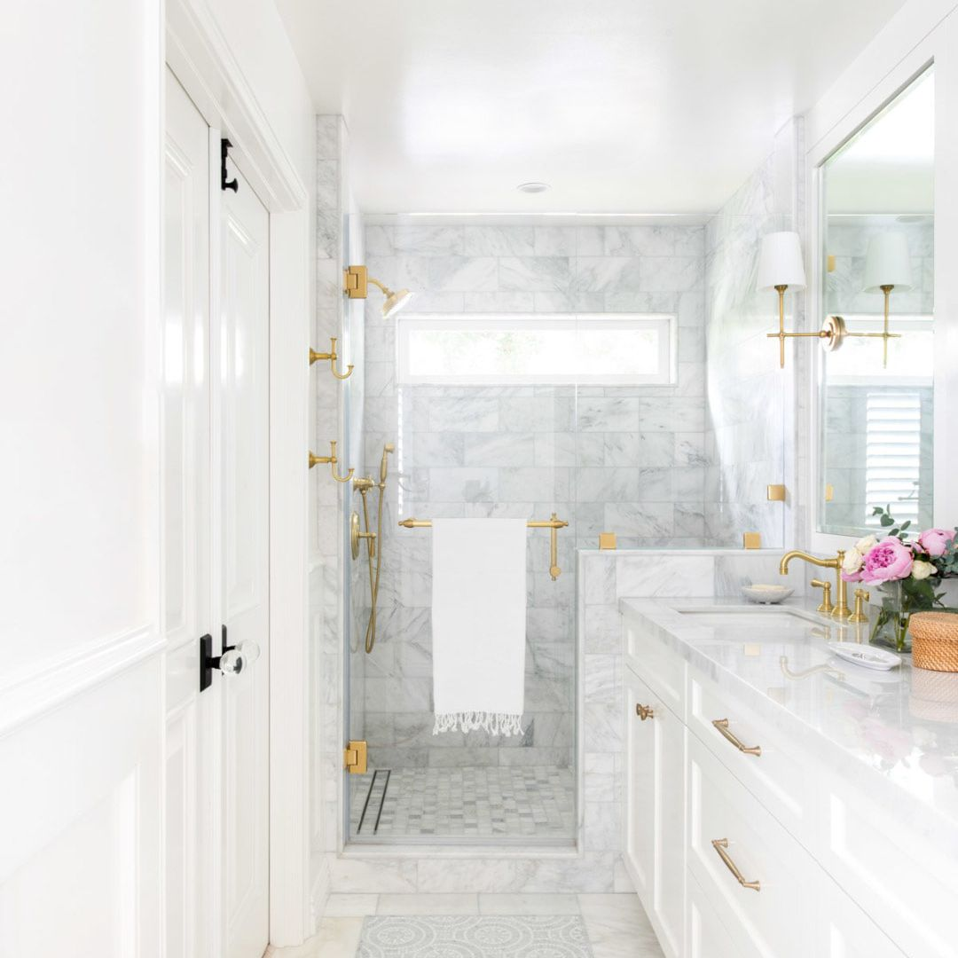 A white bathroom with a gray tile-lined shower