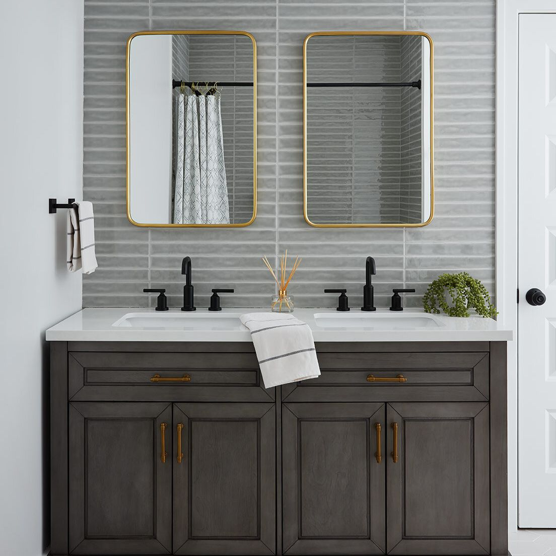 A double vanity mounted on a gray tile-lined wall