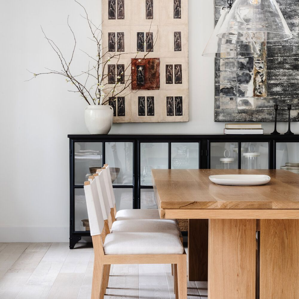 A dining room with two abstract paintings, one of which is slate gray