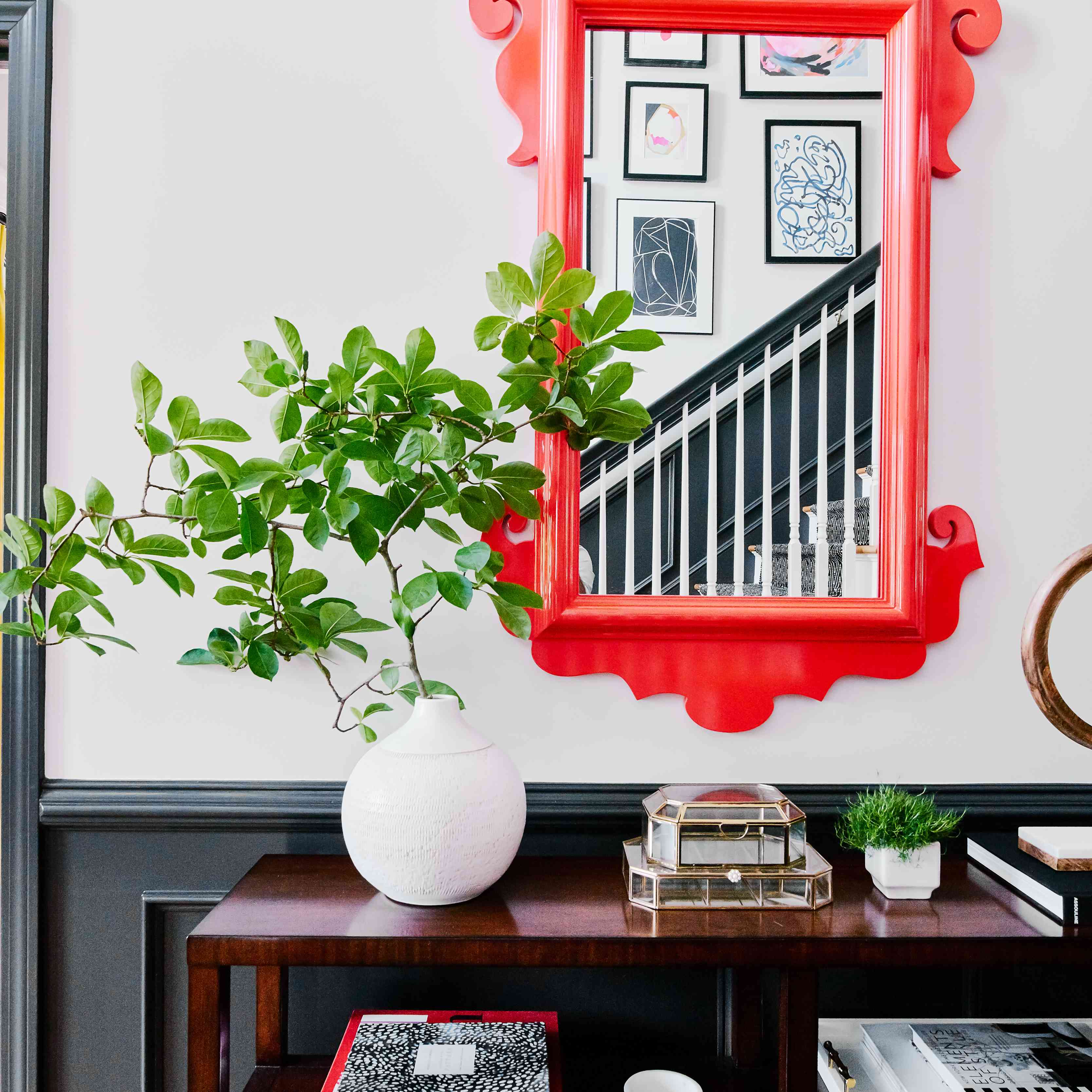entryway with dark wood table and red ornate mirror