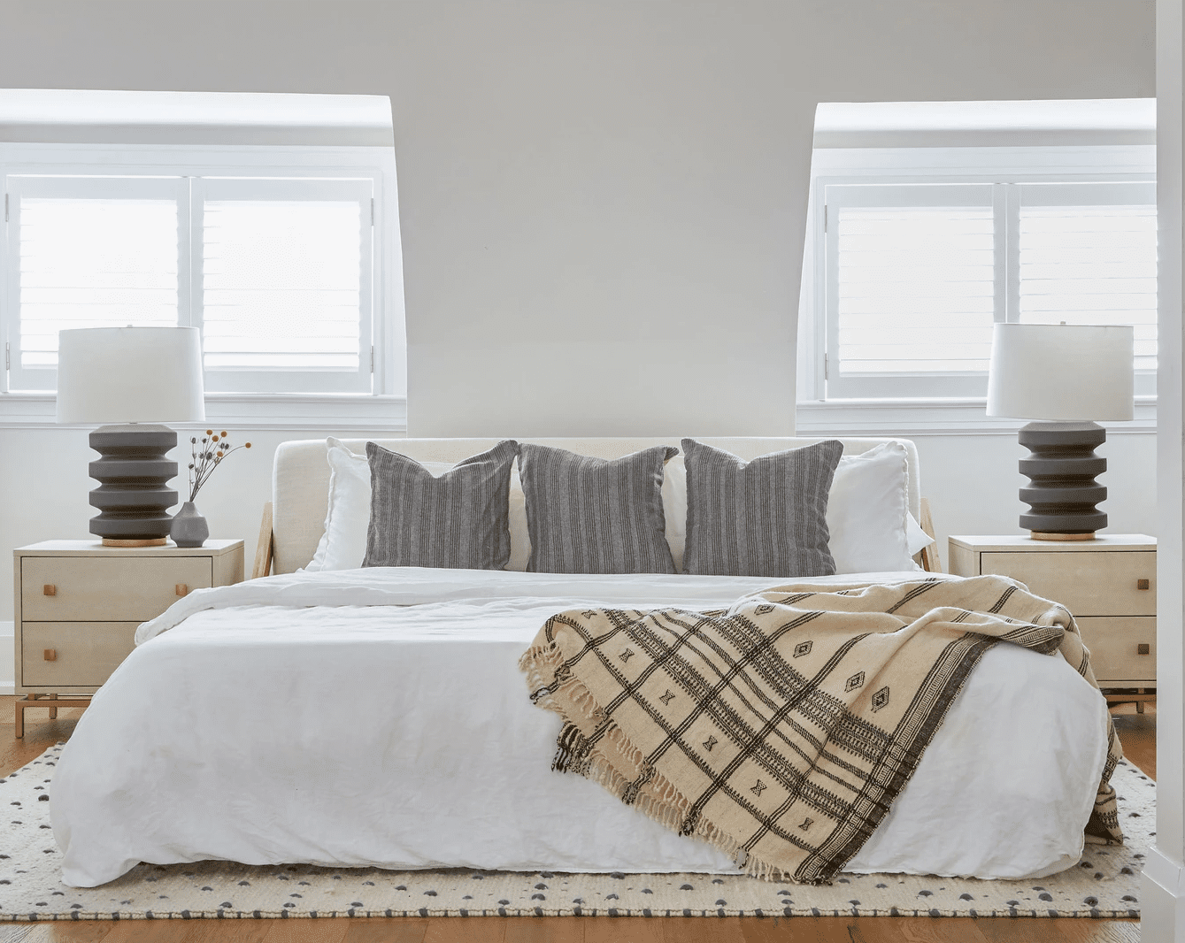 Neutral bedroom with gray pillows and lamps.
