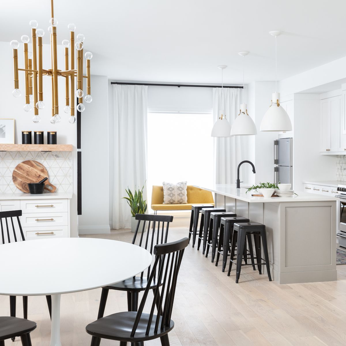 An open-concept kitchen with color-coordinated dining room chairs and bar stools