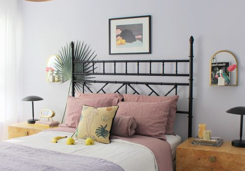 A bedroom with lavender walls, mauve sheets, and lavender blankets