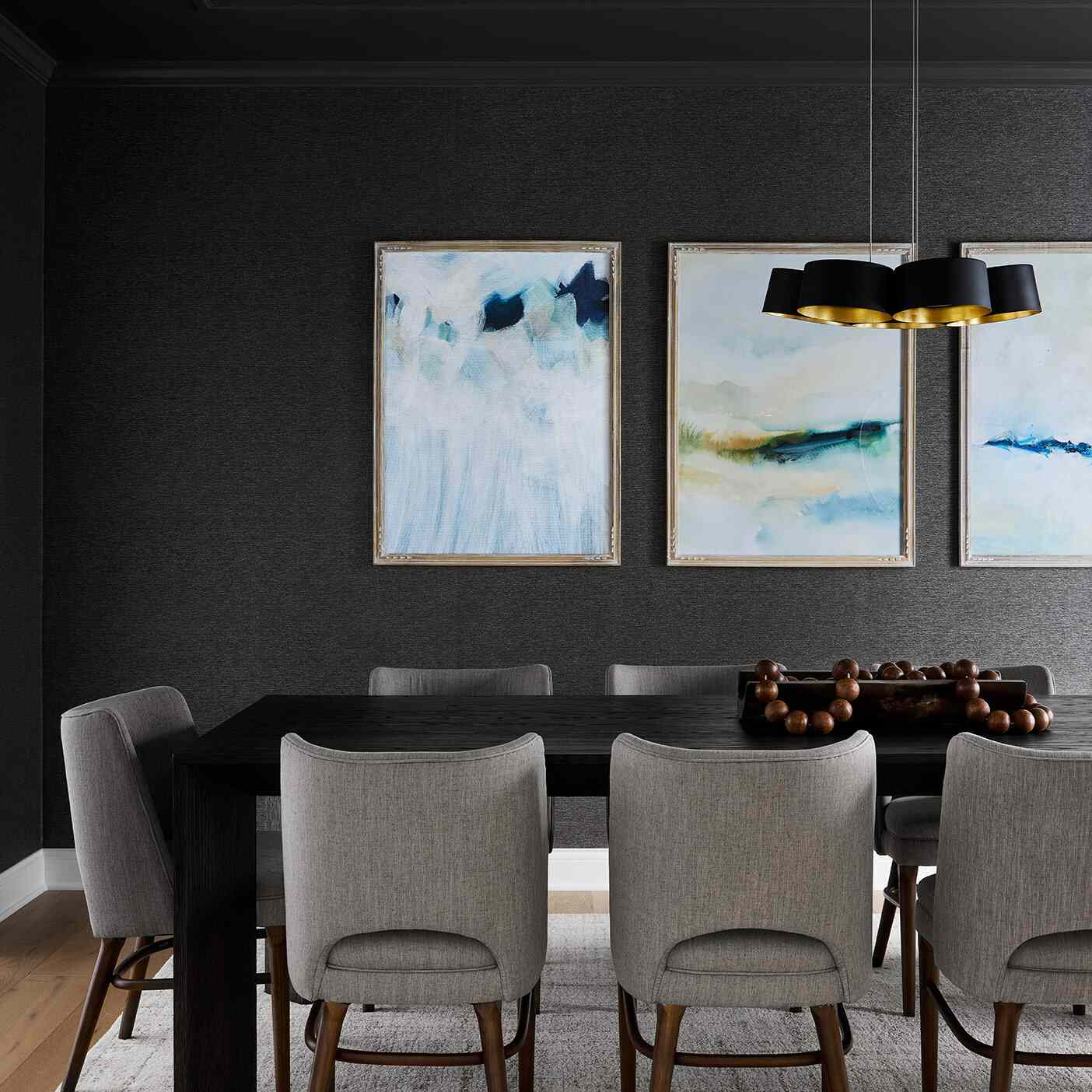 A dining room with black walls, black and gray furniture, and pastel blue art