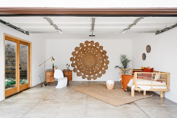 garage space with white walls, wicker couch, woven doily rug on wall