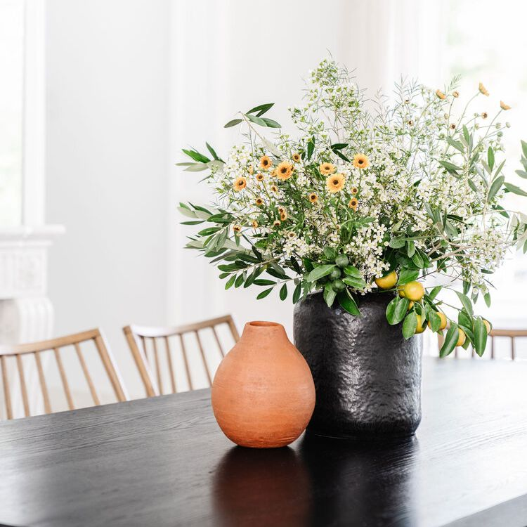 Bunch of cosmos and greenery on kitchen table.