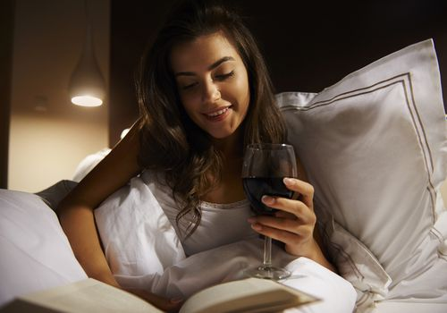 woman drinking wine and reading in bed at night