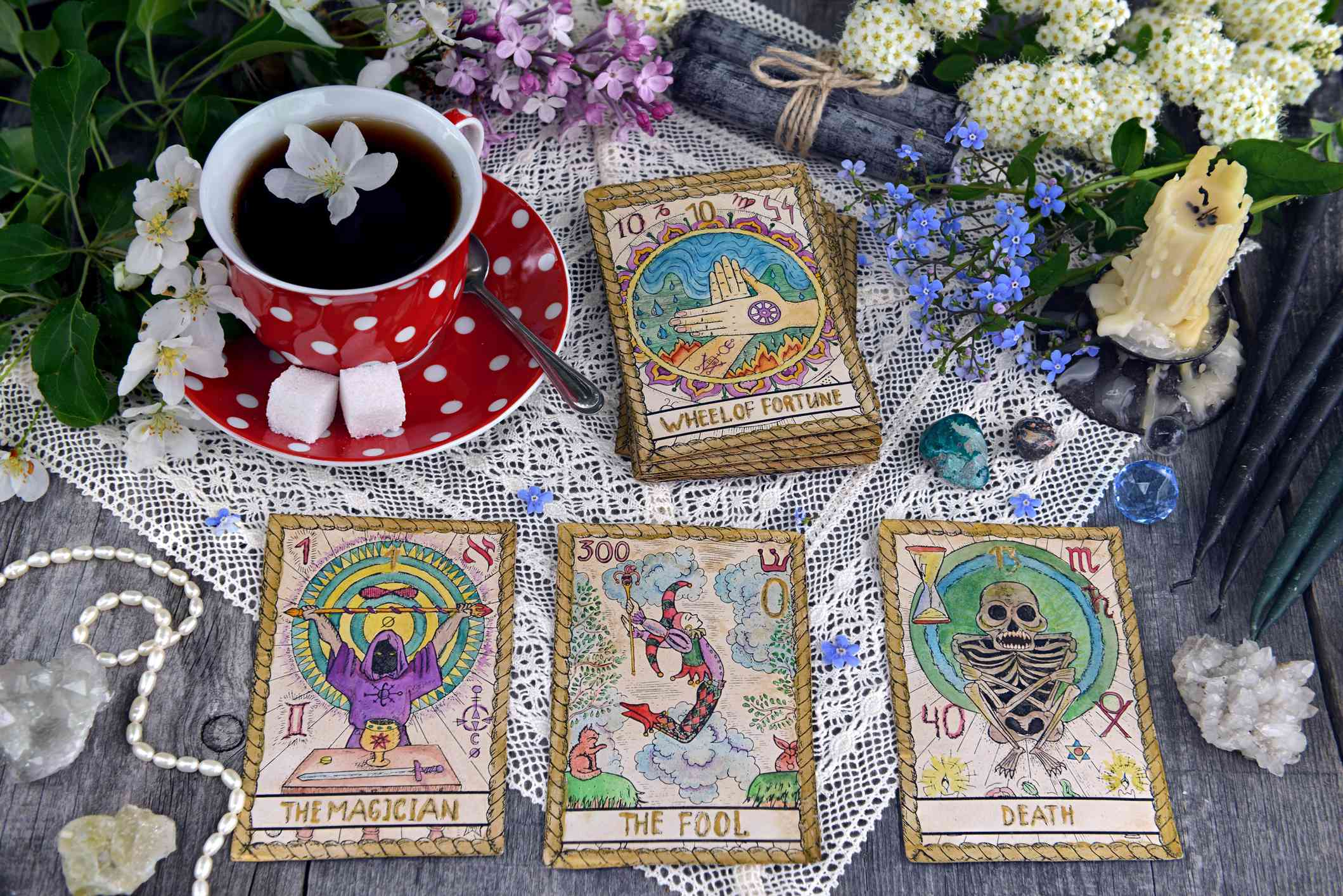 Tarot cards surrounded by fresh flowers, a cup of tea