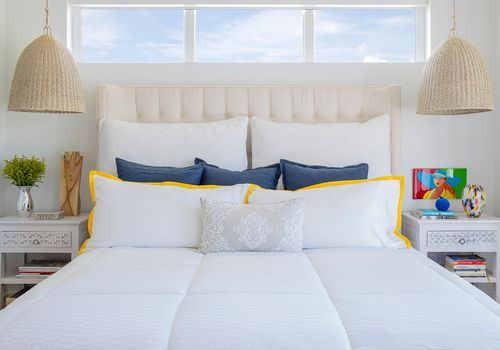 white bedroom with small pops of yellow and blue