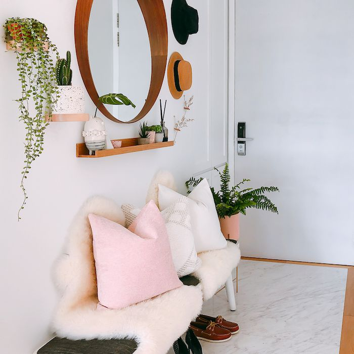 entryway with wooden circular mirror, small floating shelf, bench with accent pillows