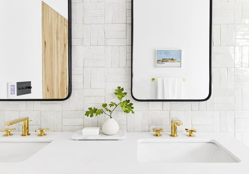 bathroom with two mirrors over his and hers sinks