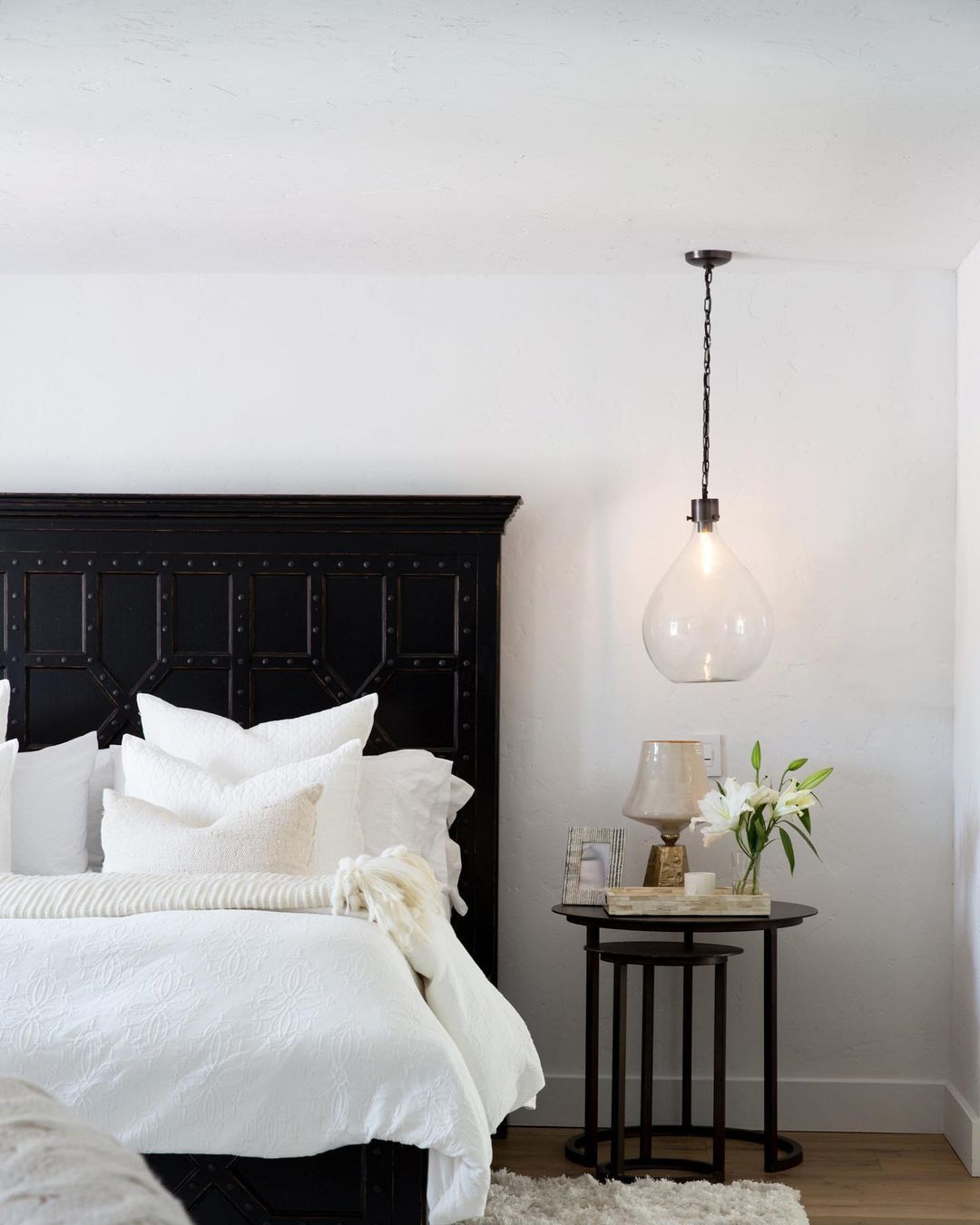Bedroom with large black bedframe and glass pendant light.