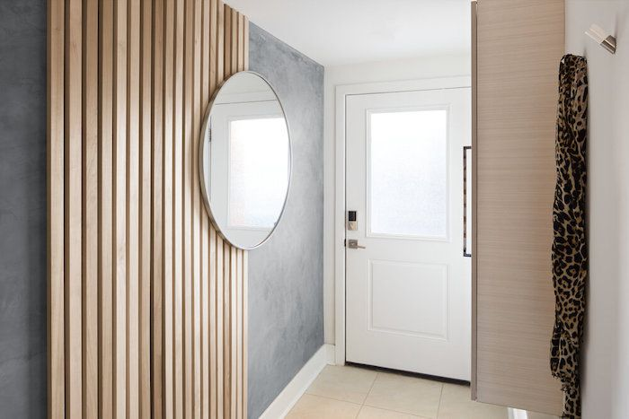 entryway with mirror, gray wall, and wooden palette