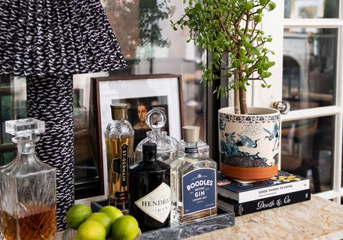 Chic bar cart with patterned lamp and small plant.
