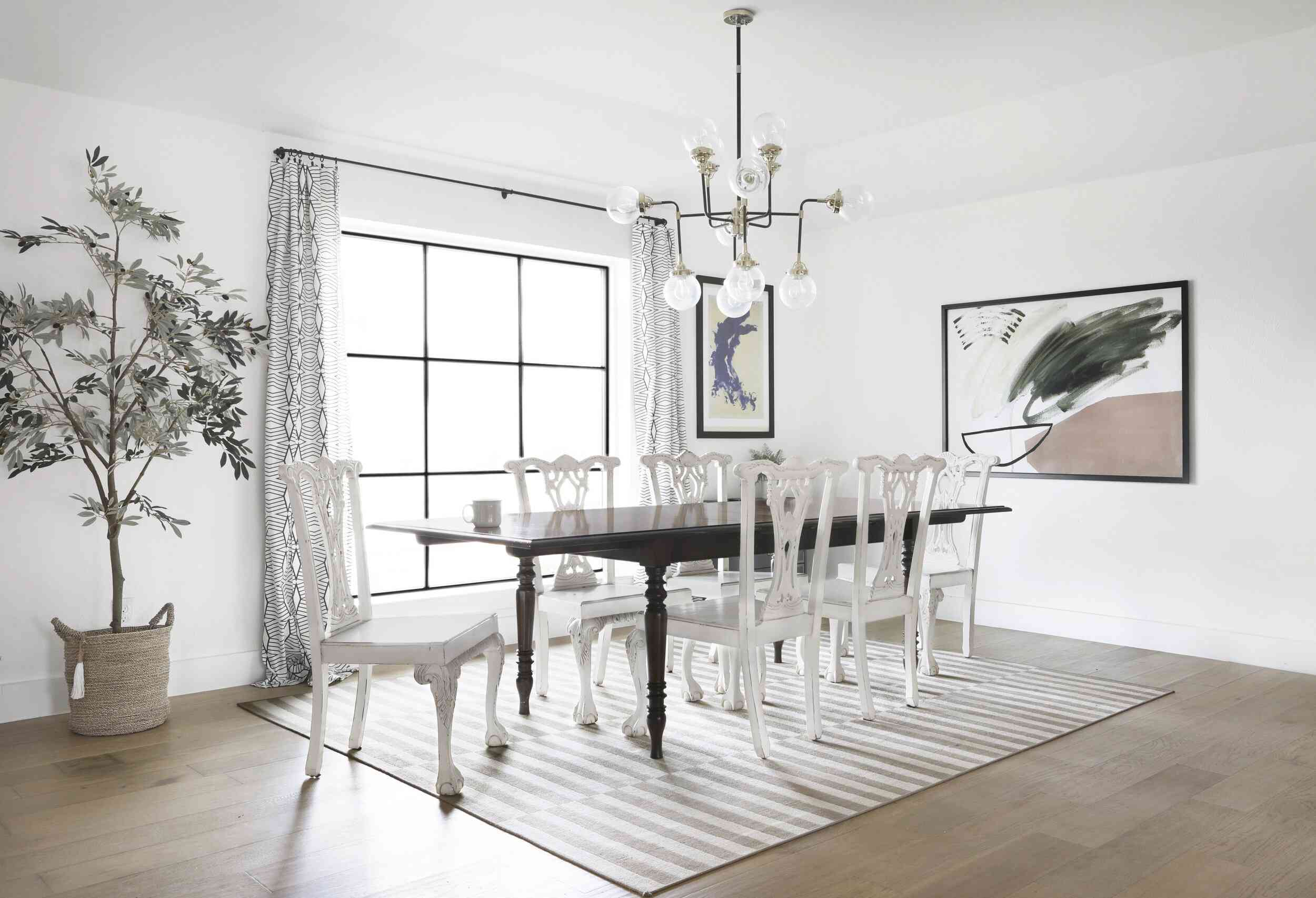 A dining room with an antique table, refurbished antique chairs, contemporary lighting, and contemporary art