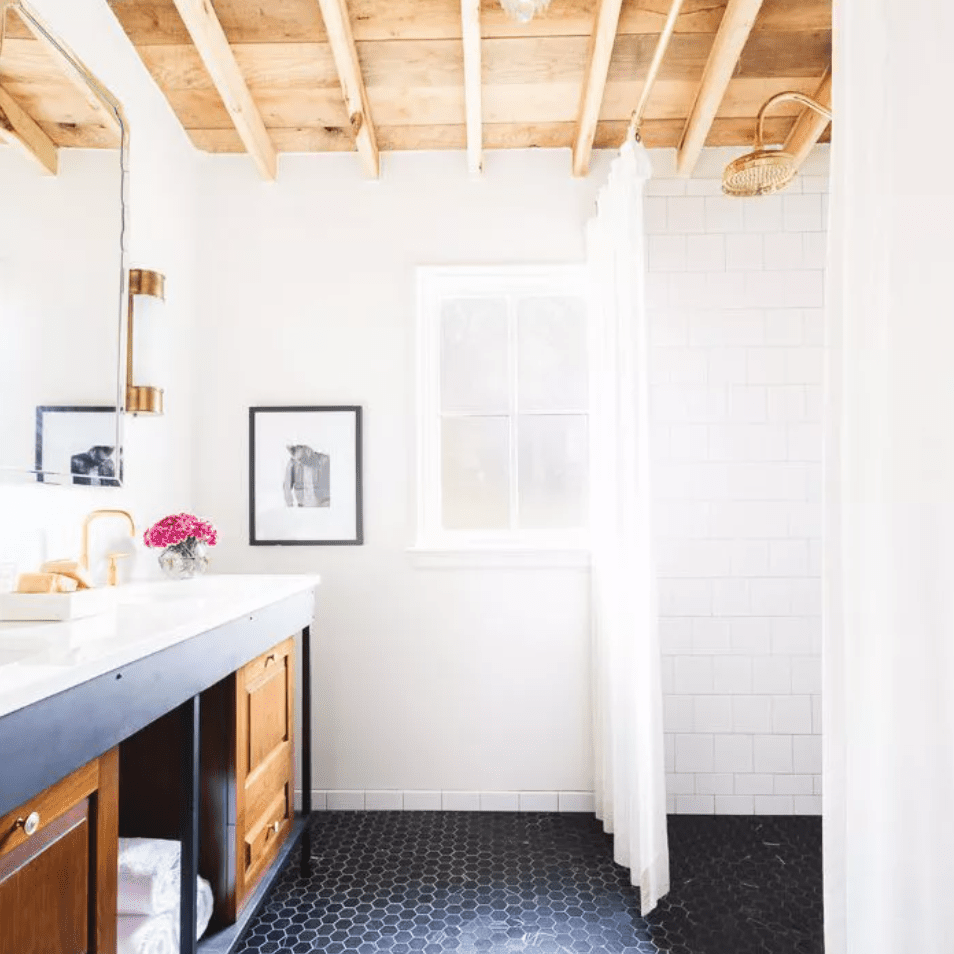 Polygonal-tiled bathroom with exposed wood-beamed ceiling and chandelier