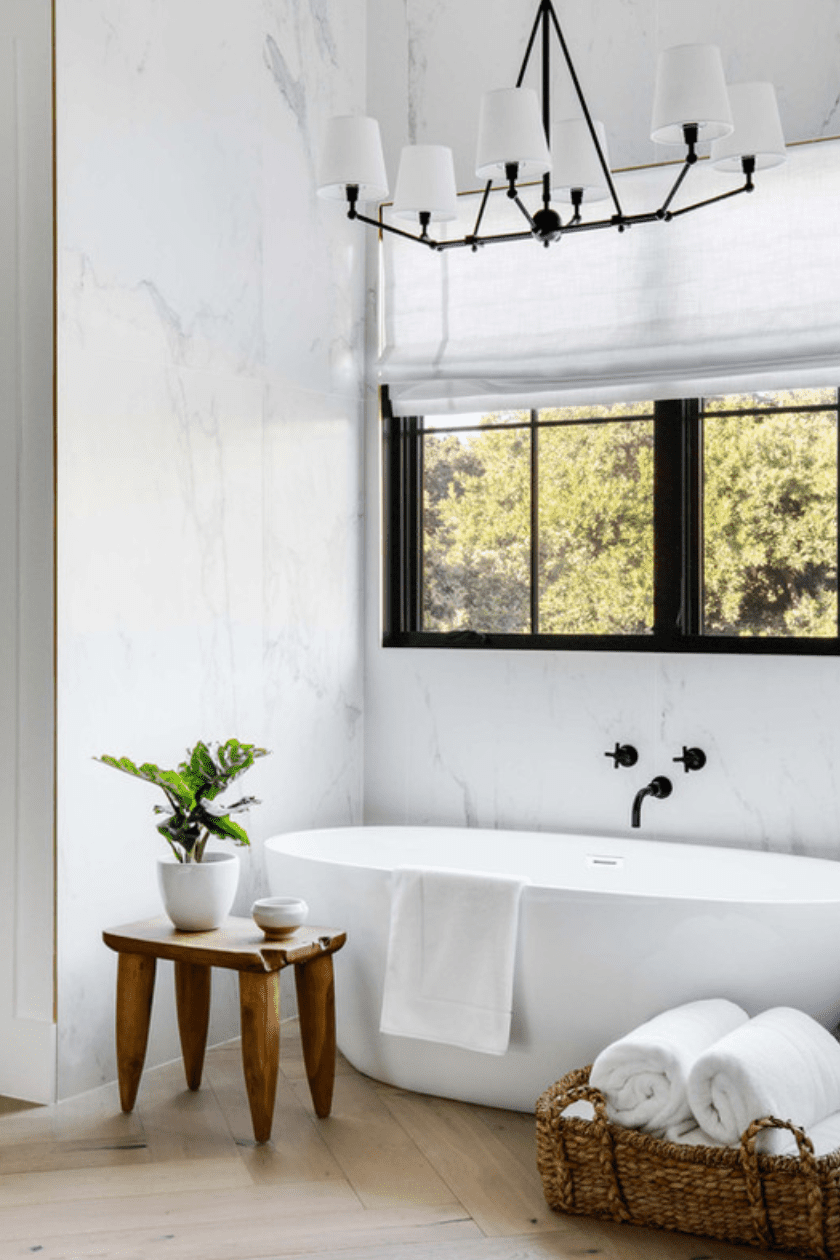 A bathroom filled with accessories, like a wooden bath stool and a woven basket full of towels
