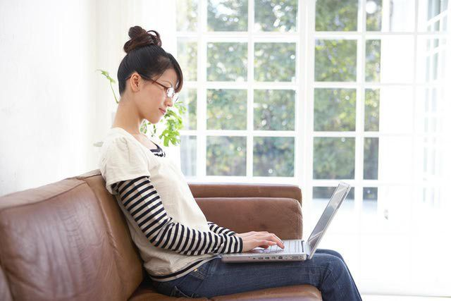 Young Asian woman typing on lap top computer