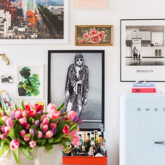 jarrón de flores frente a la pared de fotos y obras de arte