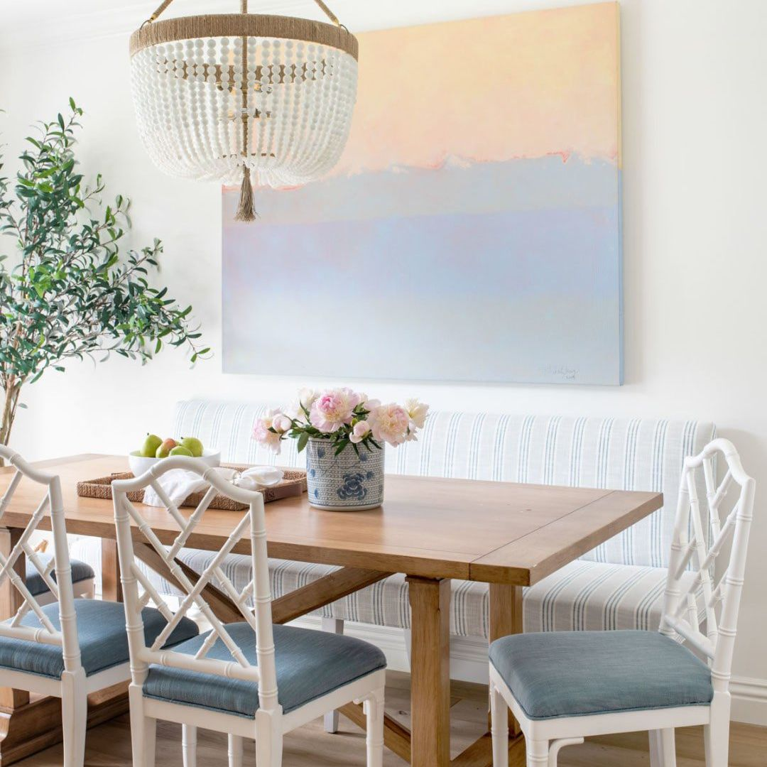 A dining room with light blue chairs and a light periwinkle painting on the wall