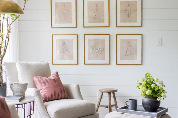 Serene sitting area with gallery wall, armchair and ottoman.