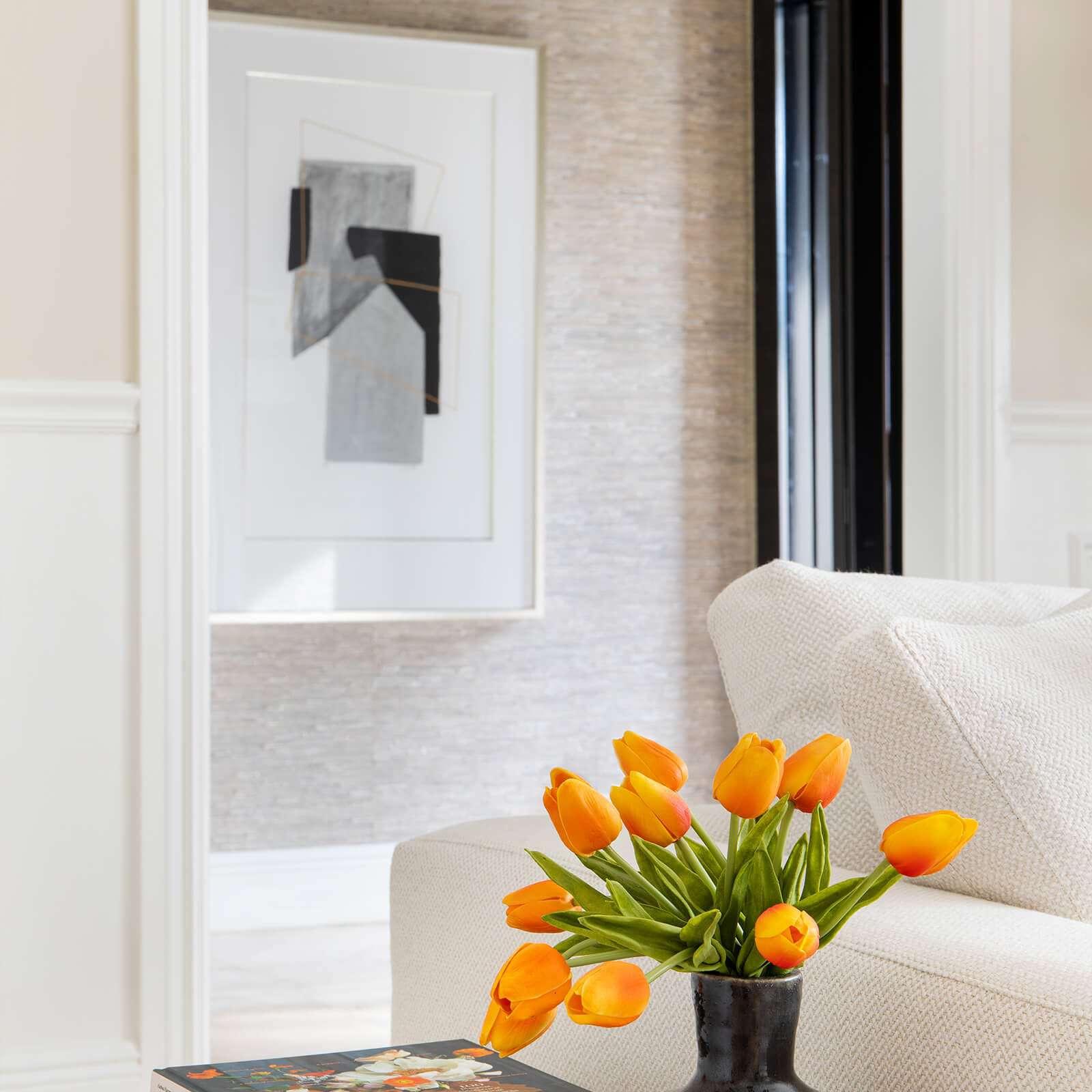 Simple foyer with sculptural light fixture, hanging art