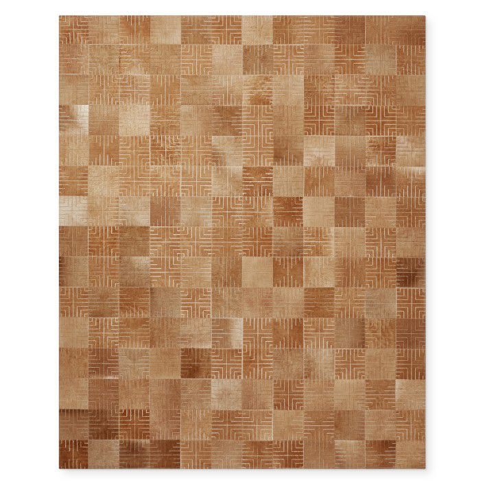 A brown patchwork hide rug with geometric designs.