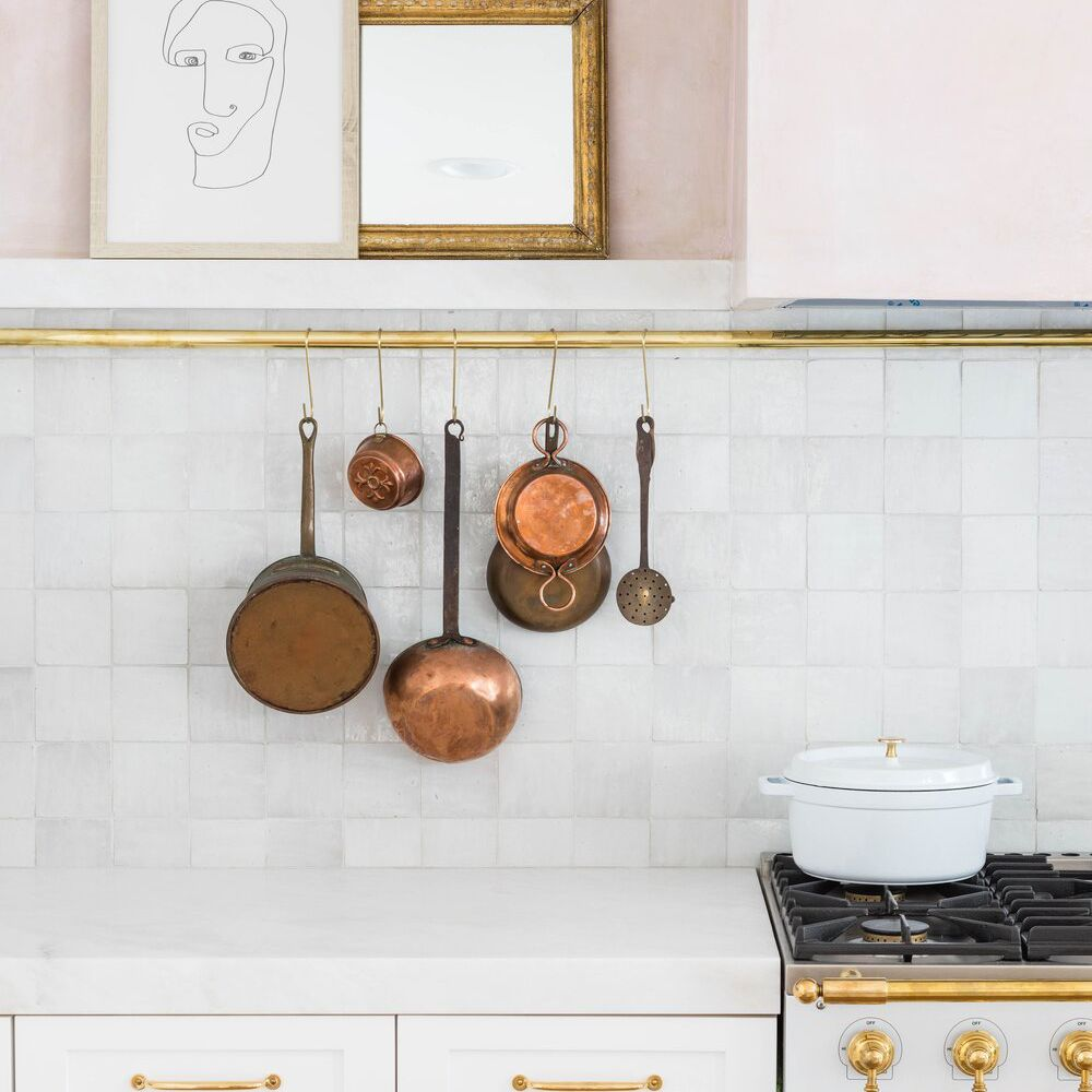 A pink and white kitchen with copper cookware