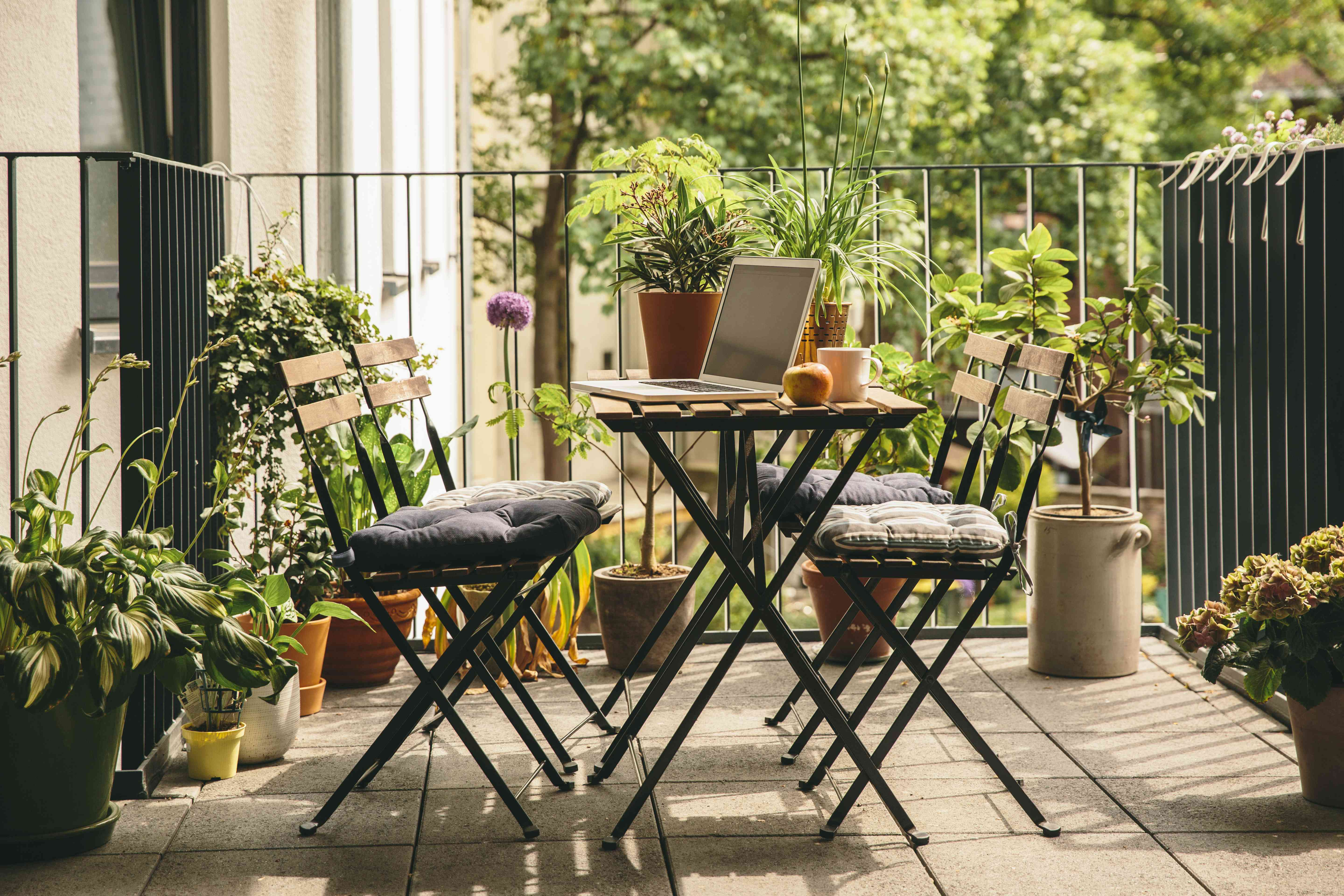 Bistro table outdoors surrounded by plants.