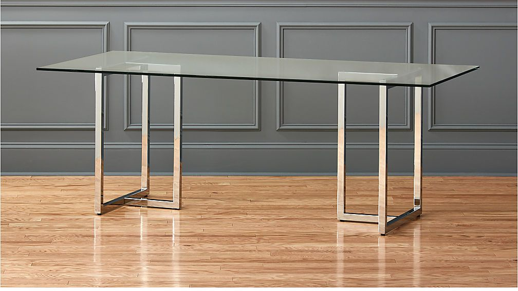 A rectangular glass-top dining table with chrome legs.