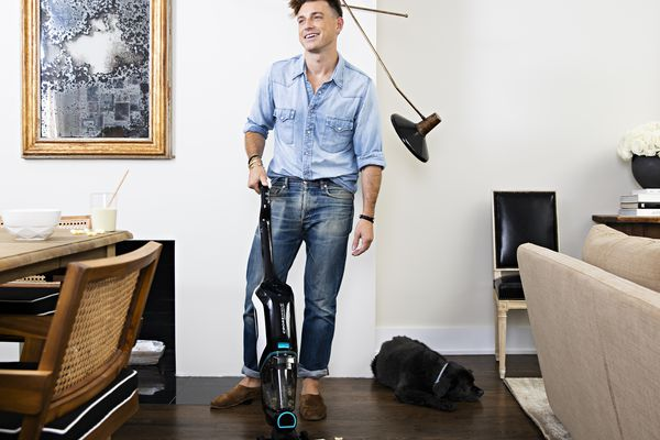 Jeremiah Brent using the BISSELL CrossWave Cordless Max vaccuum to clean up a mess in his NYC apartment.