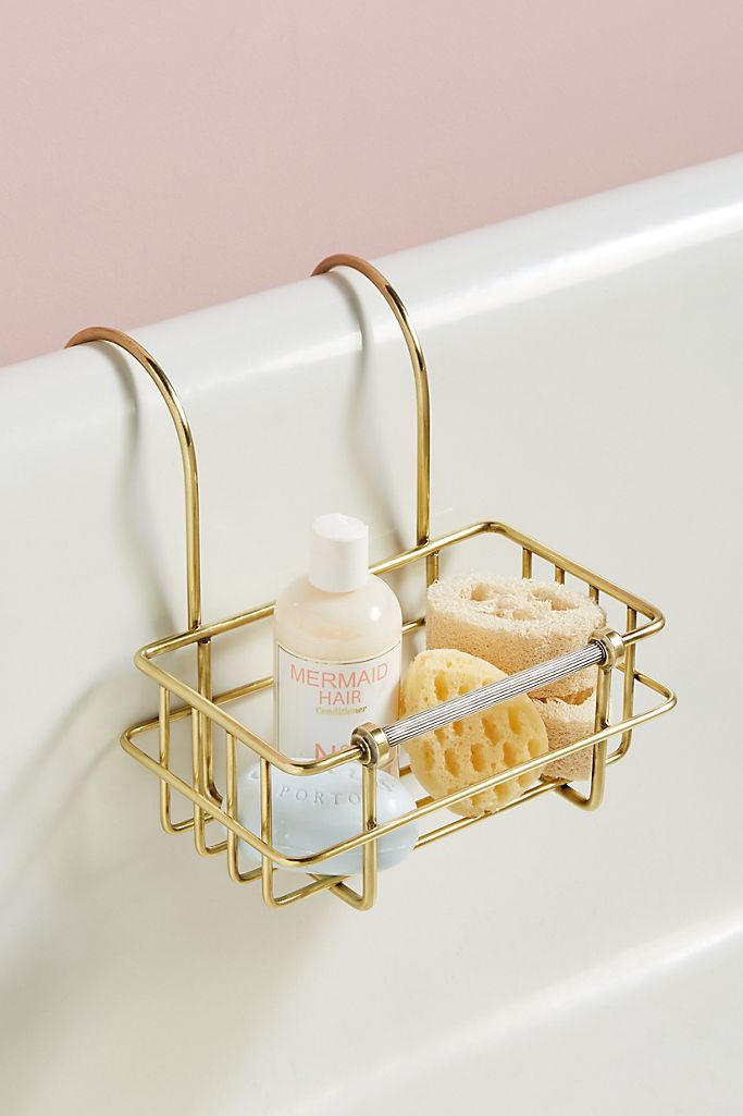 Brass bath caddy with loofas and soap in it