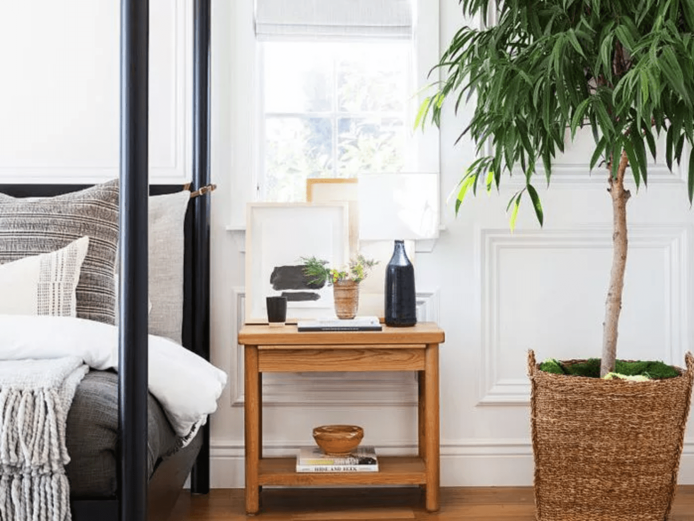 Four post bed positioned to the left of a window, a wooden nightstand positioned beneath and next to it, a potted tree