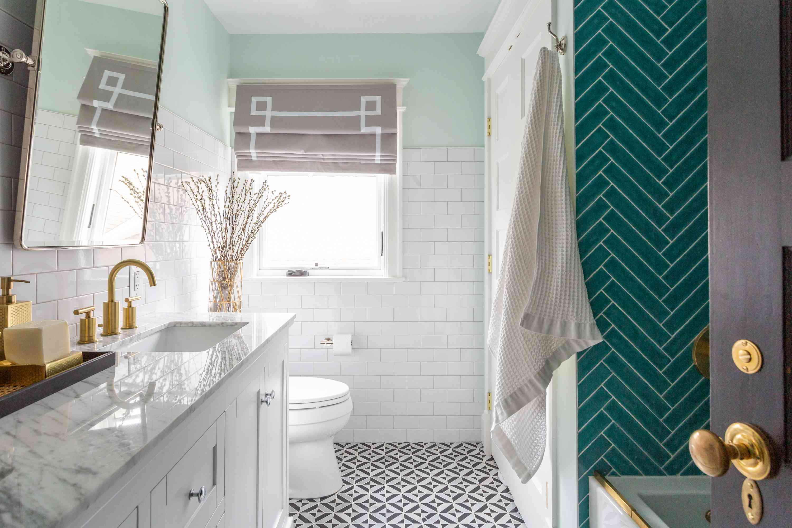 Spacious bathroom with teal tile in shower.