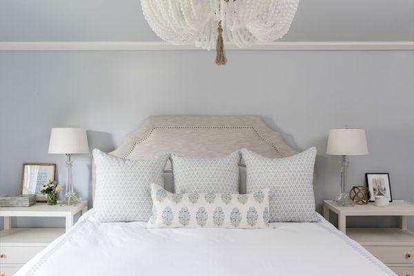 White bedding in soft blue bedroom.
