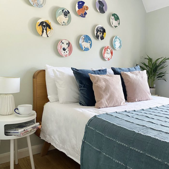 Ceramic plates painted with dogs hung on a bedroom wall
