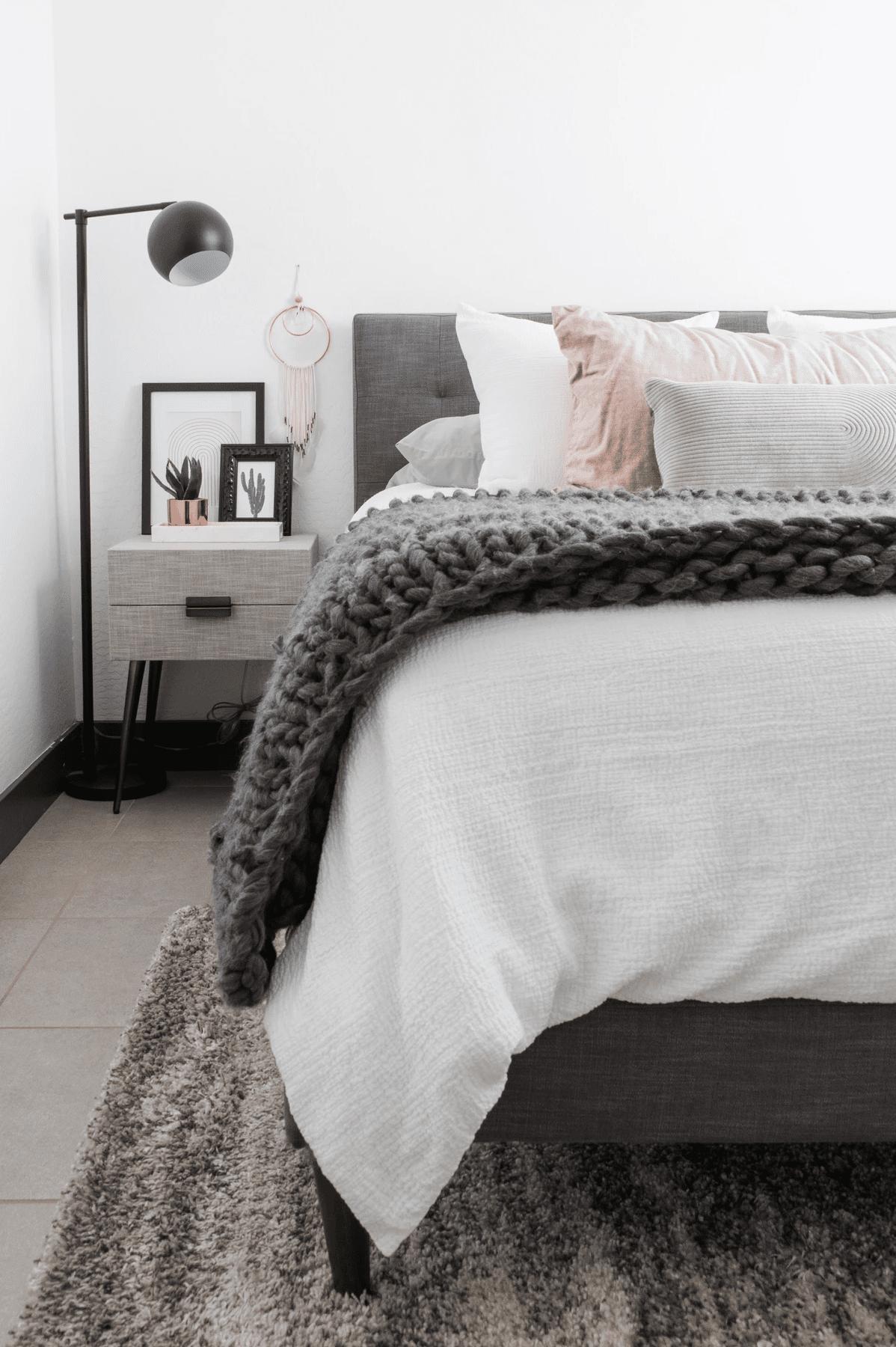 Monochrome bedroom with midcentury furniture.