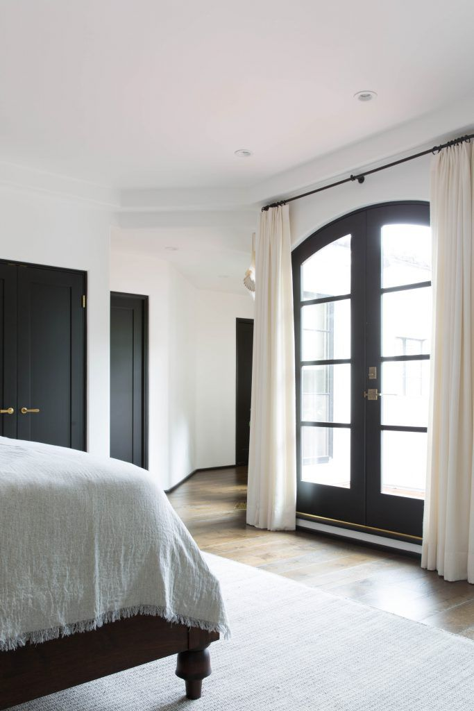 A bedroom with curtains hanging over glass doors