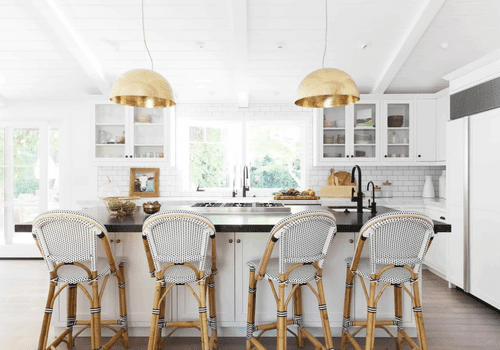 An open-concept kitchen with white woven barstools