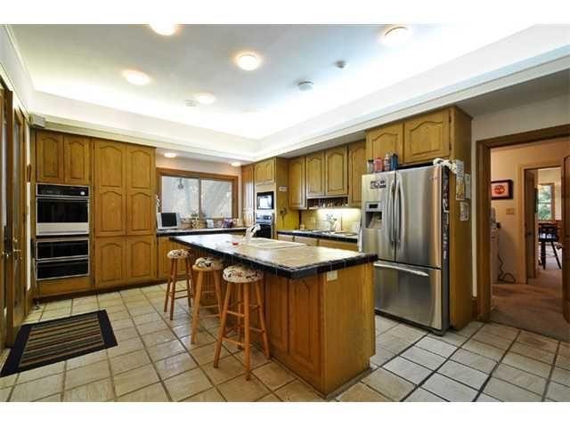 All wood kitchen with dark lighting.