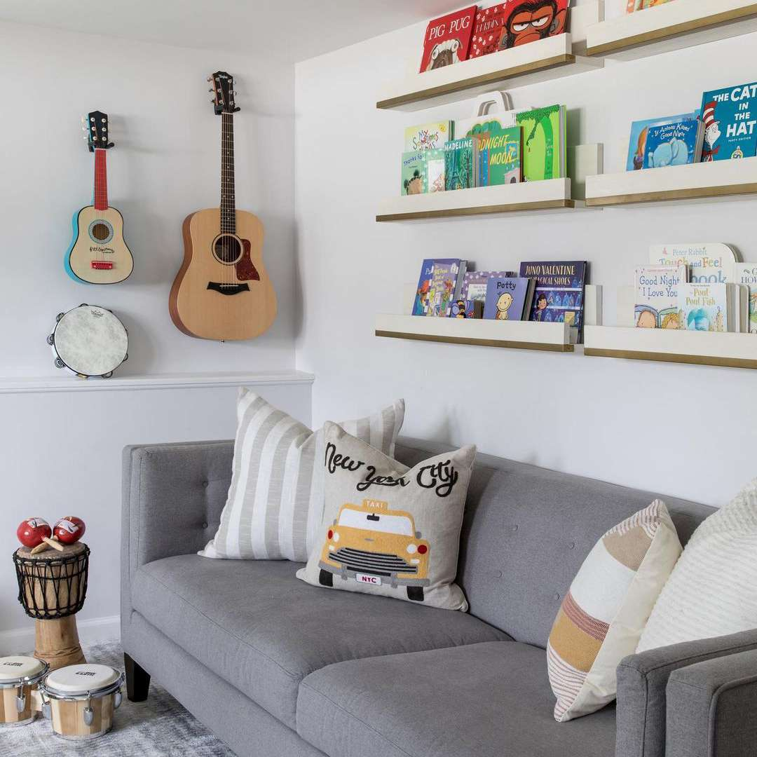 Child's play room with rainbow ombre book shelves and guitar wall decor