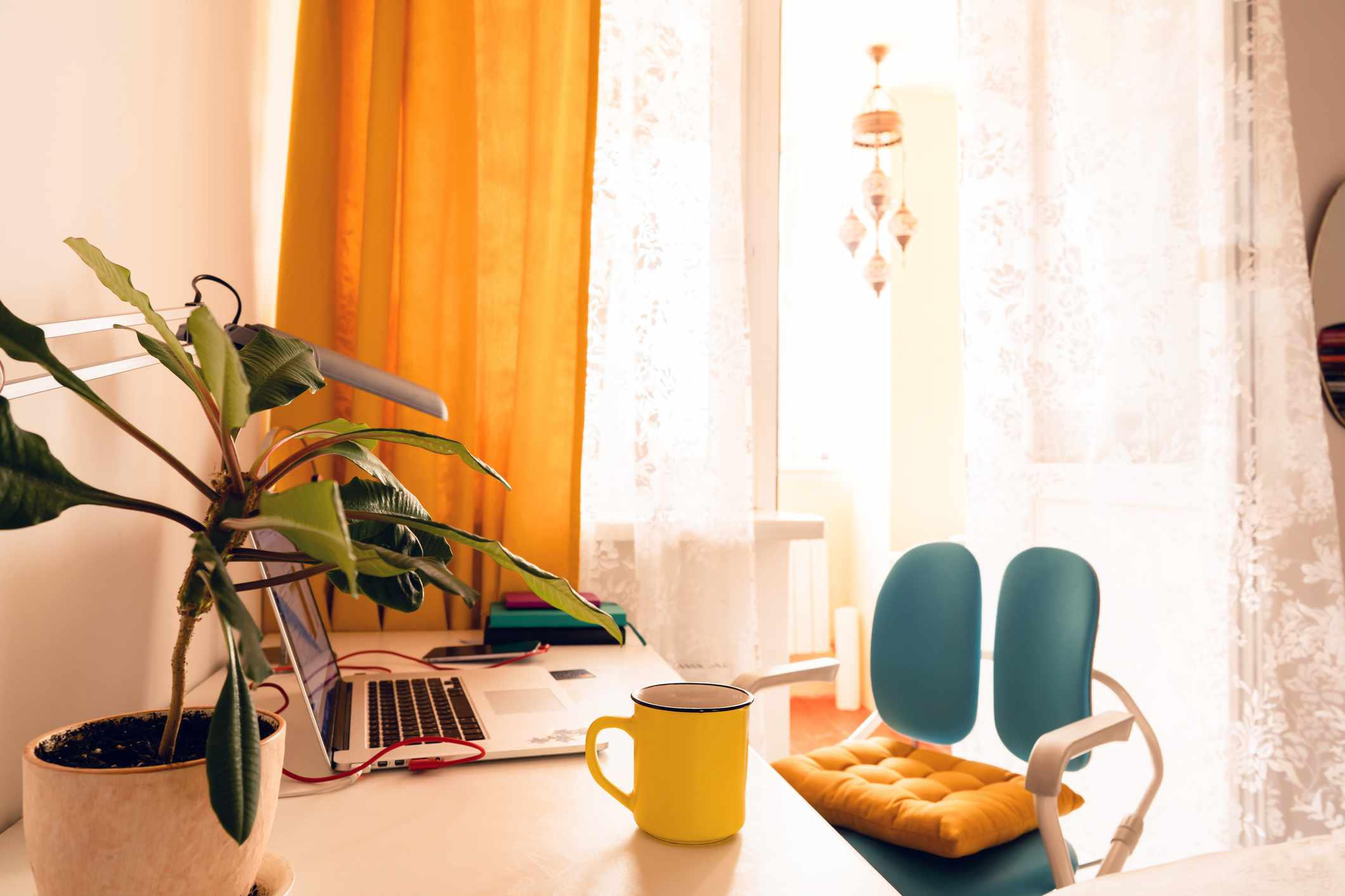 Sunny corner home office space with yellow curtains and plant on desk.