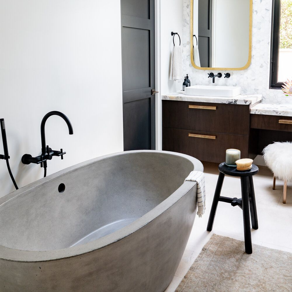 Bathroom with concrete tub, dark walnut vanity, and black and gold accents