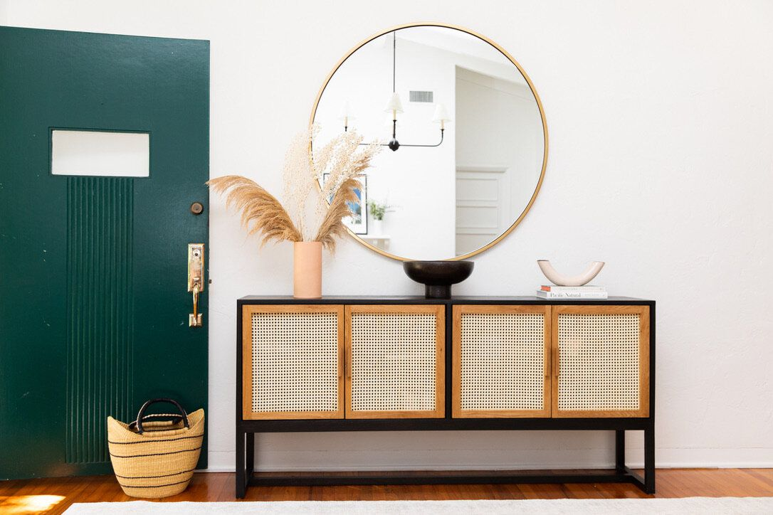 An entryway with a woven cane console table, a circular mirror, and several geometric ceramic pieces