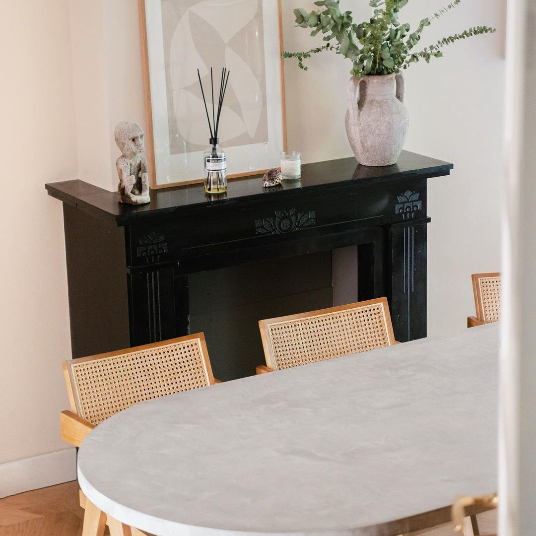 Dining table next to faux fireplace mantel.