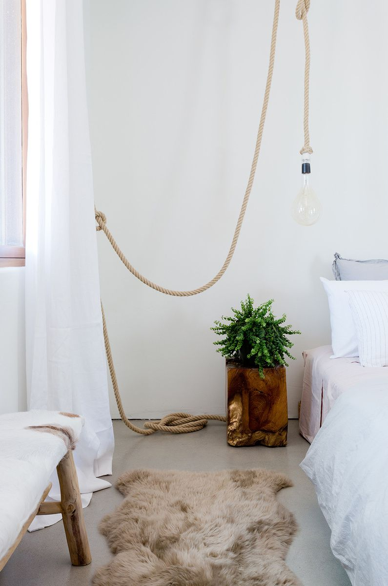White bedroom with rope and bulb light fixture