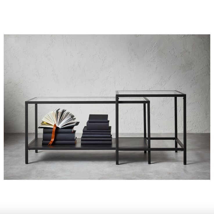 One rectangular and one square black nesting tables with glass tops.