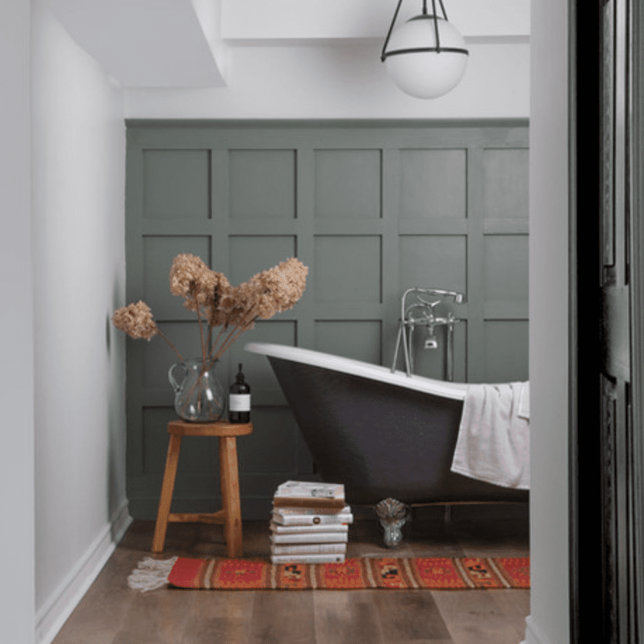 A bathroom with gray-green walls, hardwood floors, a small wooden stool, and a red printed rug