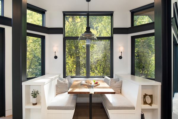 Bench seating in kitchen overlooking the trees with large windows.